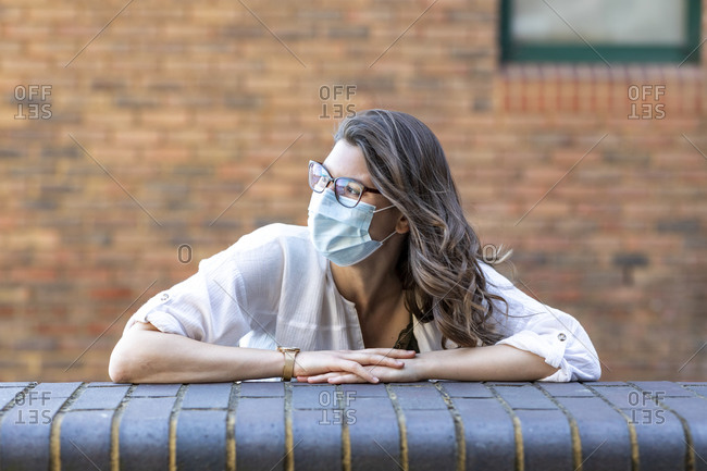 Young woman wearing protective mask looking sideways and leaning on wall