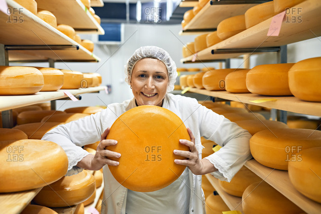 Cheese factory- smiling female worker with cheese wheel in storeroom