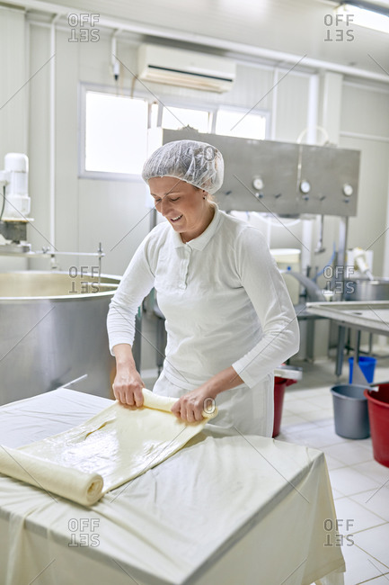 Cheese production- female worker rolling cheese- rolled layered cheese