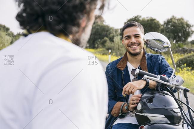Smiling man talking with biker while sitting on motorcycle