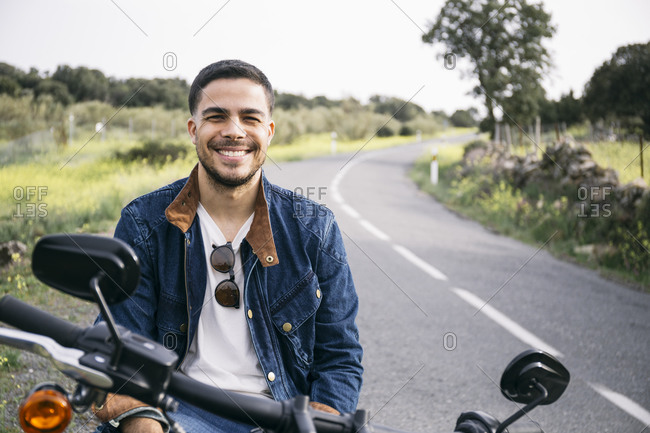Smiling young biker sitting on motorcycle in countryside