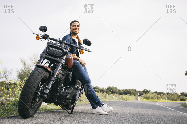 Smiling young biker leaning on motorcycle on road against sky