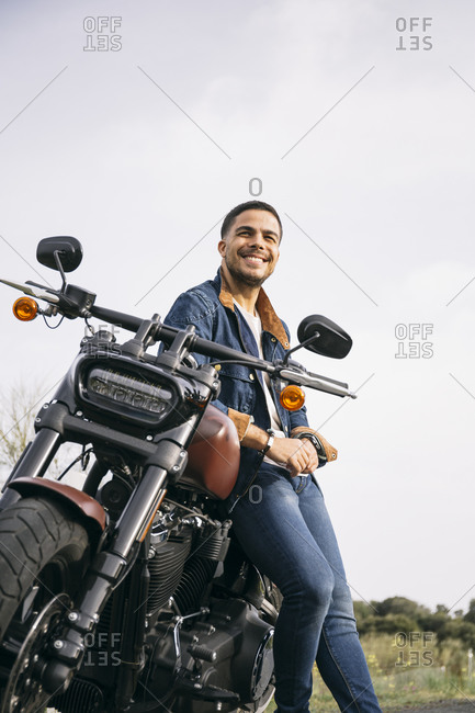 Smiling young biker leaning on motorcycle against clear sky