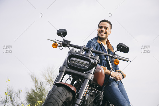 Smiling thoughtful biker leaning on motorcycle against clear sky