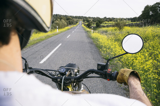 Mature man riding motorcycle on road amidst plants