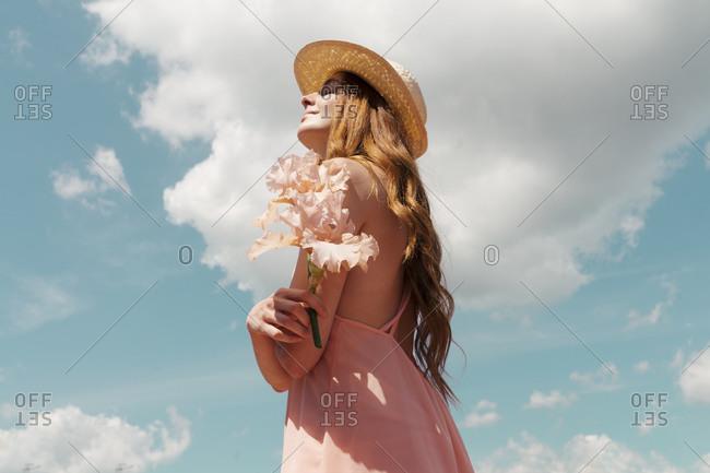 Portrait of redheaded woman with flower enjoying sunlight