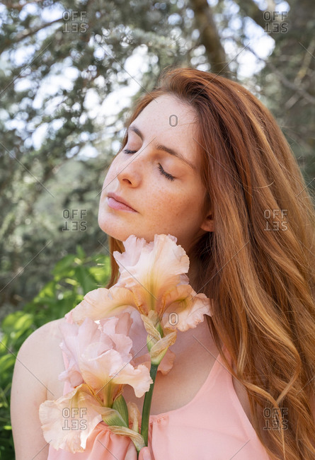 Portrait of redheaded woman with rosy flower and closed eyes