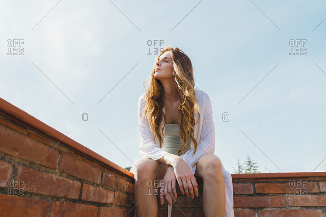 Redheaded woman sitting on rooftop and enjoying view sitting on wall
