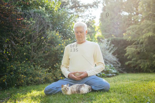 Senior man meditating with cat in garden