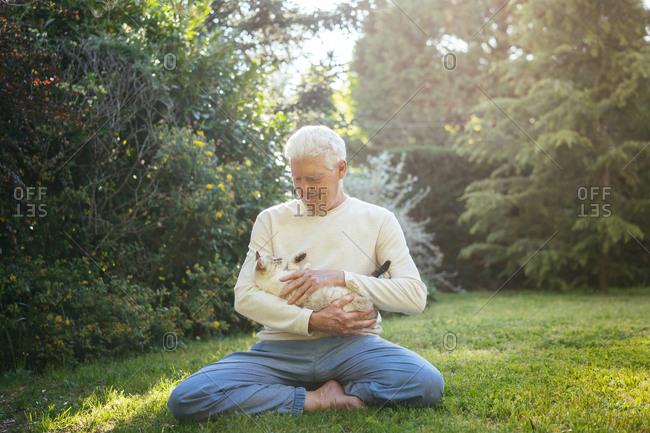 Senior man cuddling with his cat in garden