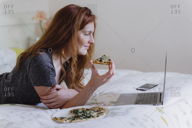 Young woman with long brown hair watching movie on laptop while enjoying pizza in bedroom