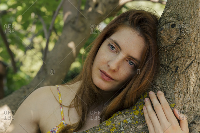 Thoughtful young woman looking away while leaning on tree trunk in garden