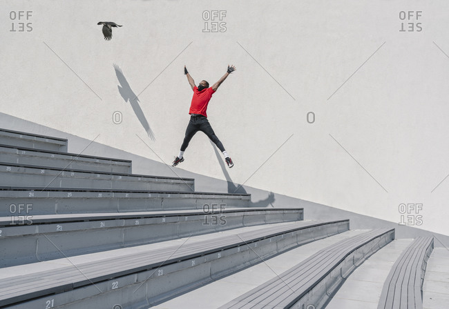 Sportsman wearing face mask jumping on stairs with flying bird