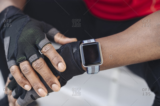Close-up of sportsman wearing smartwatch and gloves