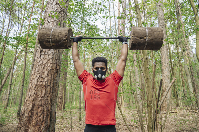 Sportsman with face mask exercising with wooden barbells in the forest
