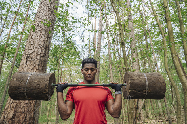 Sportsman exercising with wooden barbells in the forest