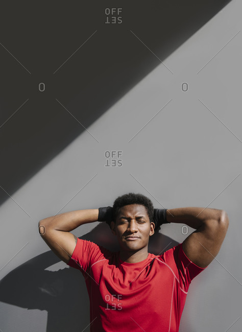 Portrait of sportsman with closed eyes at grey wall