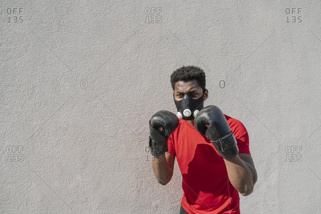 Portrait of a sportsman wearing face mask and boxing gloves at a wall