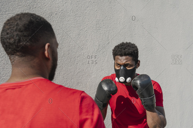 Sportsman wearing face mask and boxing against training partner