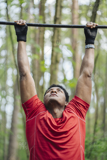 Sportsman exercising at high bar in the forest