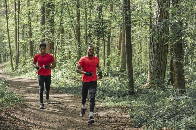 Sportsmen running on forest path