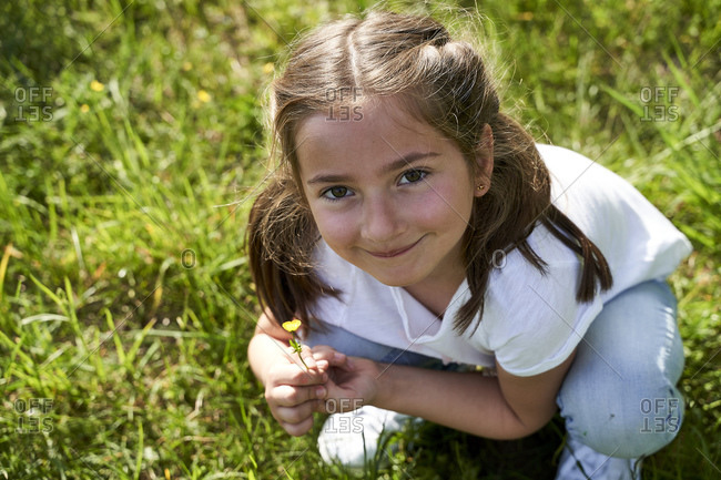 Cute girl crouching while holding tiny yellow flower on sunny day
