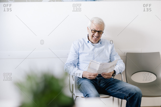 Senior man sitting in waiting room of medical practice- reading leaflet