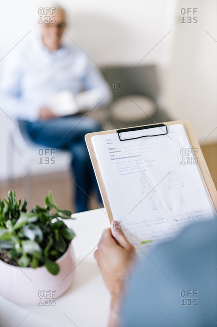 Woman holding clipboard with patient's record at the reception of physiotherapist's practice