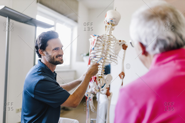 Physiotherapist explaining treatment to patient- using skeleton