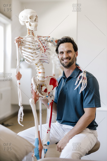 Physiotherapist sitting in practice with skeleton arm around his shoulder