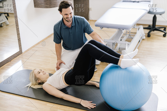 Physiotherapist assisting female patient- practicing with fitness ball- lying on gym mat