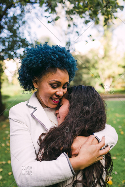 Loving mother with blue hair embracing daughter while standing in park