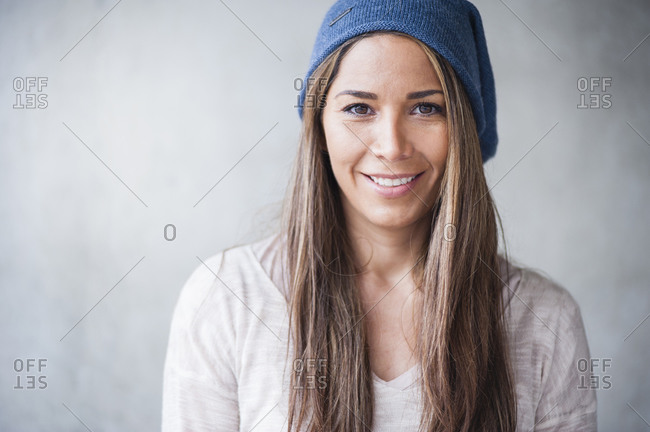 Happy woman with long brown hair wearing knit hat against gray wall