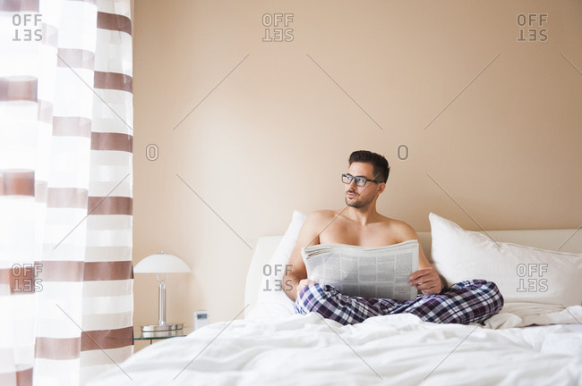 Thoughtful man holding newspaper while sitting on bed at home