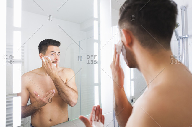 Reflection of young man applying shaving cream on cheek at home