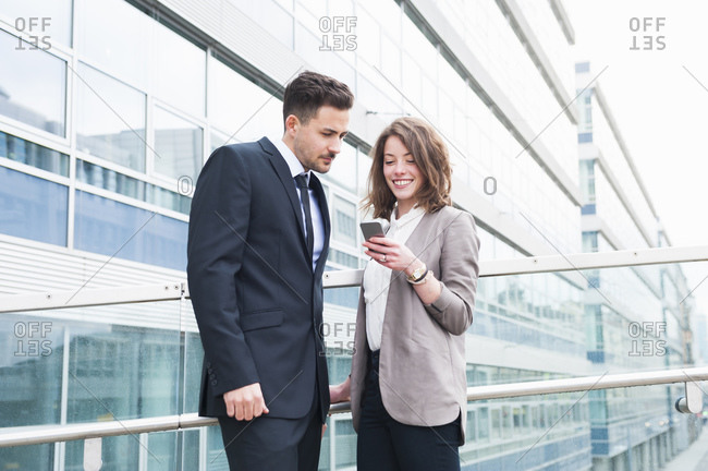 Happy business couple using smart phone while standing outside office building
