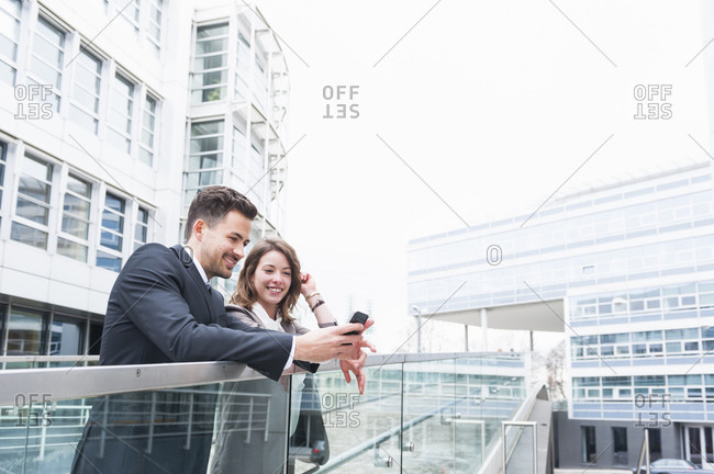 Business couple using smart phone on elevated walkway outside office building