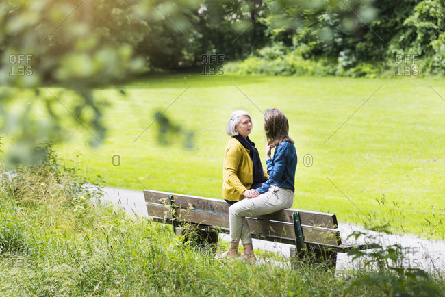 Senior woman and adult daughter sitting on backrest of park bench talking together