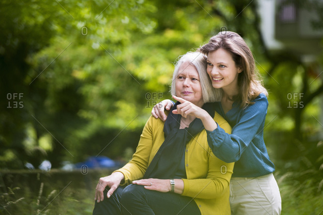 Portrait of senior woman and adult daughter watching something in a park