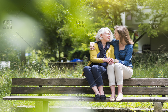 Senior woman and adult daughter sitting on backrest of park bench looking at each other