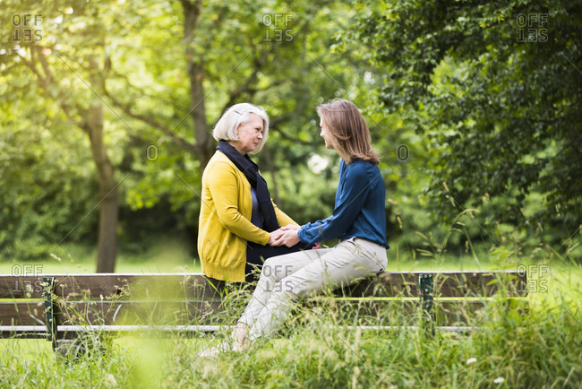 Senior woman and adult daughter sitting on backrest of park bench holding hands
