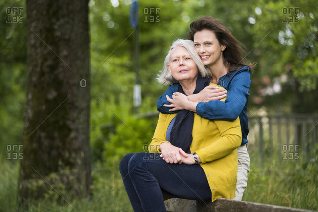 Portrait of happy woman hugging her mother sitting on backrest of a park bench