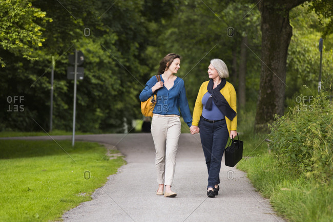 Smiling senior woman and adult daughter walking hand in hand in a park looking at each other