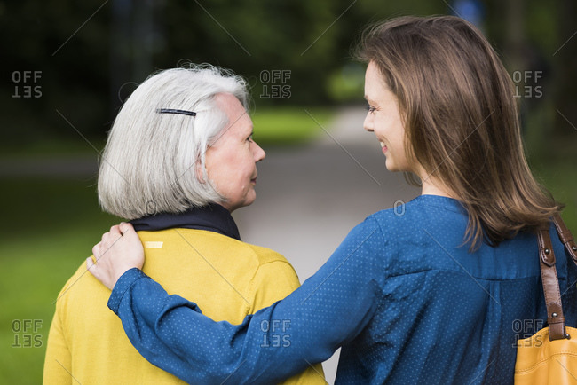 Senior woman and adult daughter looking at each other in a park