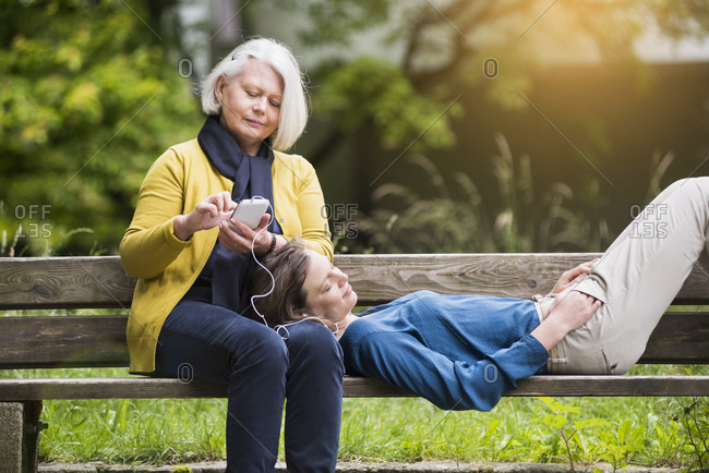 Senior woman and adult daughter relaxing together on a park bench