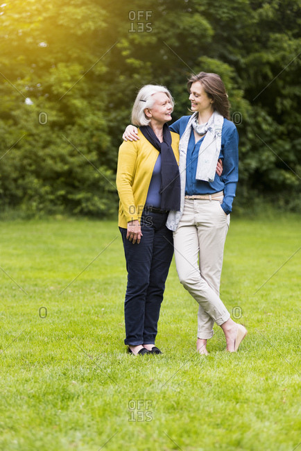 Happy senior woman and adult daughter standing on a meadow in a park looking at each other