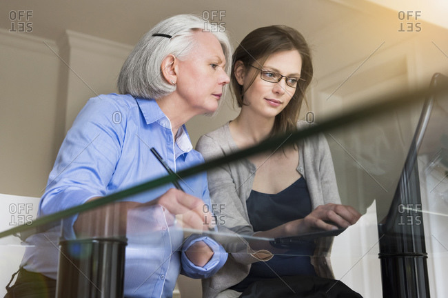 Portrait of senior woman and adult daughter working together on laptop