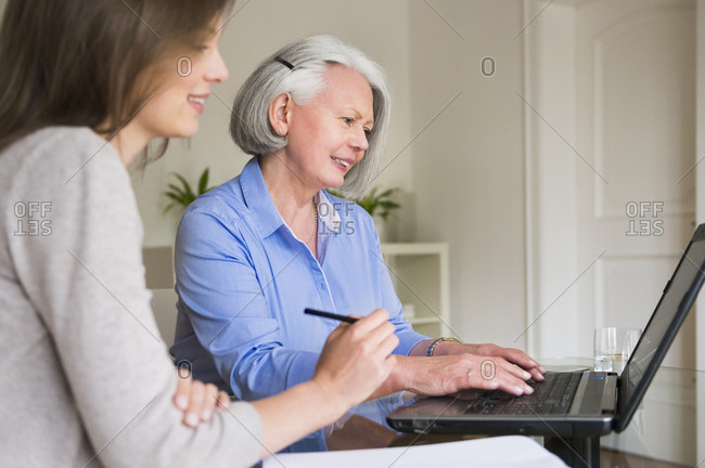 Portrait of senior woman working on laptop while her adult daughter watching her