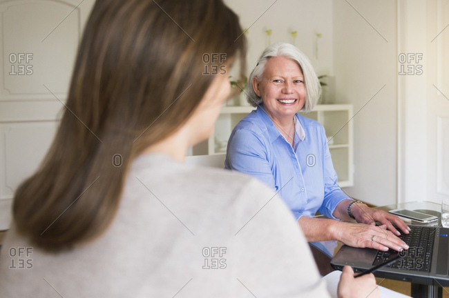 Portrait of smiling senior woman working on laptop looking at her adult daughter