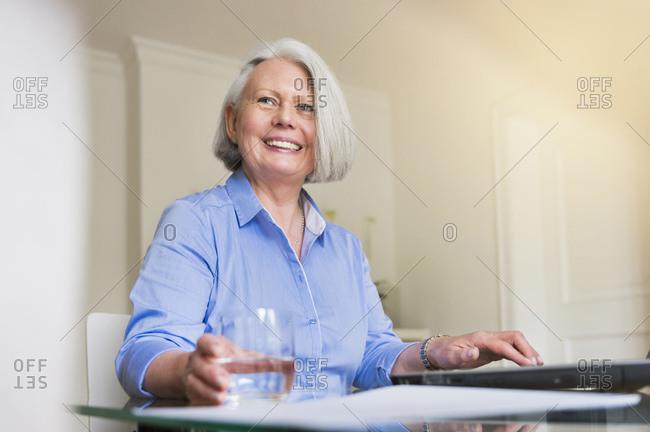 Portrait of smiling senior businesswoman working on laptop